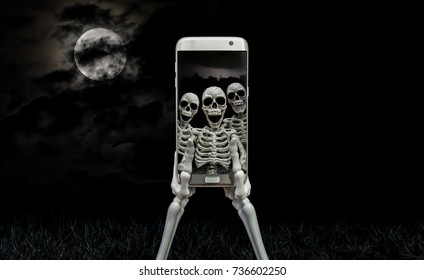 Scene showing skeleton hands holding a modern cell phone that has been used to take a selfie of three skeletons.