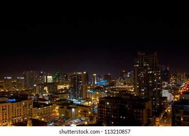 Scene of tall buildings lit at night from high up in downtown San Diego, California