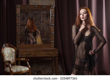 scene of temptation. model posing near the mirror in the boudoir room. woman in erotic underwear stands in a sexual pose