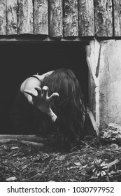 Scene of terror, girl on the ground with hair on her face with her arm outstretched crawling out of a basement