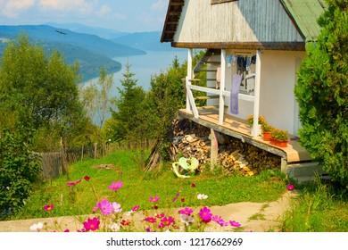Scene with typical Romanian house in green flowering garden by Muntelui mountain lake, Izvorul Muntelui, Neamt, Romania