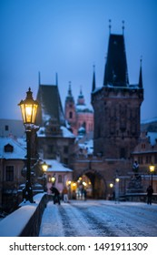 Scene from winter Prague. Old lamppost on the Charles Bridge with the Lesser Town Bridge Tower in the background.