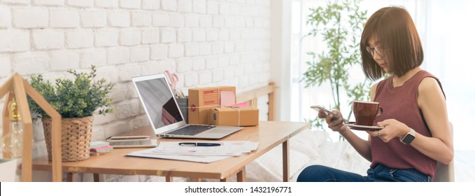 Scene of woman hold coffee cup prepare to work at desk with laptop and small parcel box use smartphone, home office dimension photo for banner