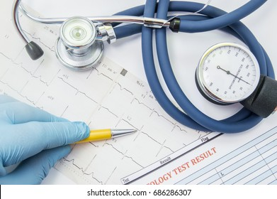 The scene with the work of cardiologist or general practitioner. The physician indicates to the patient pathological ECG which lies next to a stethoscope, a blood analysis result and sphygmomanometer