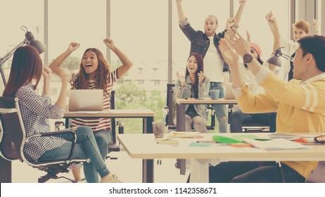 Scene of young creative woman celebrating project success with group of Asian and Multiethnic Business people with casual suit in the modern workplace, people business group concept