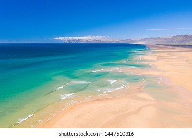 Scenery above view of tuquoise water and waves and sandy beach of Raudasandur