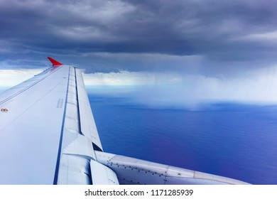 Scenery from airplane 's window viewing airplane's wing and typical thunderstorm over southwestern Pacific Ocean , New Zealand