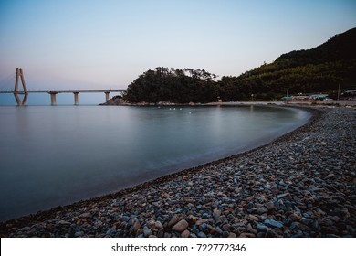 Scenery of the bay consist of many little rocks on the beach, mountain and bridge