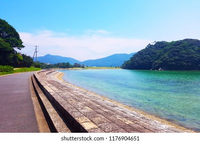 Scenery of the beautiful wide green emerald pond and the big mountain islands near the asphalt curved walking street in Goto Island, Nagasaki, Japan.