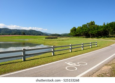 Scenery bicycle lane in  lake park with blue sky and mountain forest background.