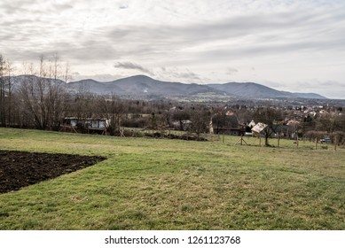 scenery of Bystrice nad Olsi village with hills of Moravskoslezske Beskydy mountains on the background in Czech republic during mostly cloudy autumn day