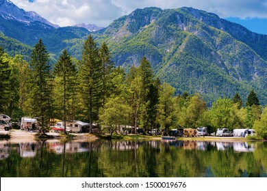 Scenery with camping of RV caravan trailers near Bohinj Lake in Slovenia. Nature and camper motorhomes in Slovenija. View of motor home van and green forest. Landscape in summer. Alpine Alps mountains