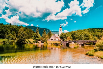 Scenery and Church of St John Baptist on Bohinj Lake of Slovenia. Nature in Slovenija. View of blue sky with clouds. Beautiful landscape in summer. Alpine Travel destination. Julian Alps mountains
