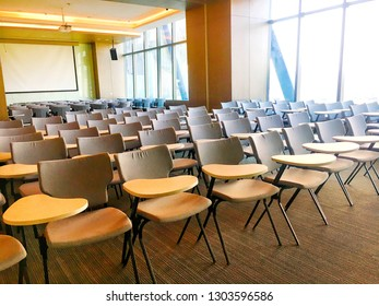 Scenery in the classroom, with a light brown chair for writing books. With a projector and screen with soft light in the morning