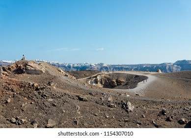 Scenery of desert covered with volcanic rock and gravel at Nea Kameni Volcanic Park and Tholos Naftilos, volcanic island in Santorini, Greece.