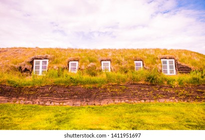 Scenery of desolate village with mountains, houses with grass roof, Iceland. Traditional Farm Houses in Skaftafell National Park, Iceland. Typical icelandic houses covered with grass
