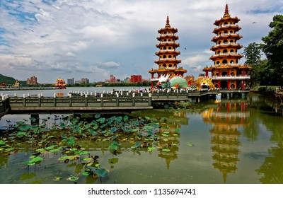Scenery of Dragon & Tiger Pagodas by Lianchihtan Lotus Lake, a popular tourist attraction in Zuoying, Kaohsiung Taiwan, with waterlilies under Nine-Turn Bridge & reflections of the towers in the water