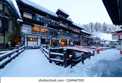 Scenery of Ginzan Onsen after snowfalls, a hot spring town in Obanazawa, Yamagata, Japan, with bridges over a stream flanked by antique wooden buildings of Japanese Ryokan on a cold winter morning