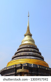 Scenery of golden vitage buddhist pagoda with clear blue sky background. Thailand. The religious statue of peaceful. vertical view.