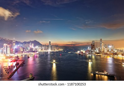 Scenery of Hong Kong at nightfall, with a city skyline of modern skyscrapers by Victoria Harbour between Kowloon & Hongkong Island and ships navigating in the busy seaport under beautiful twilight sky
