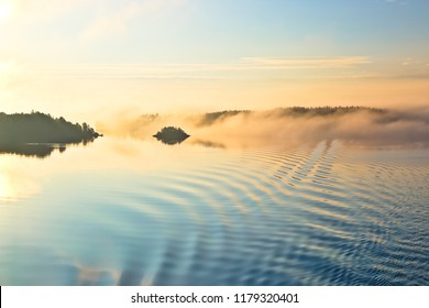 scenery of islands in early morning with clouds floating on the sea and reflection of morning light in stockholm archipelago sweden