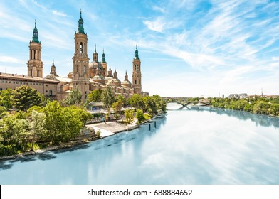 Scenery landscape with Basilica of Our Lady of Pillar. Blue sky reflects in clear water. Green trees along river.