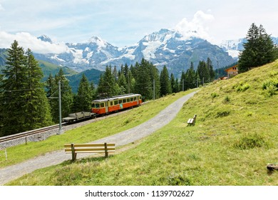 Scenery of a local train traveling on a green grassy hillside & wooden benches by a hiking trail facing majestic Eiger, Monch & Jungfrau mountains in background in Murren Bernese Oberland, Switzerland