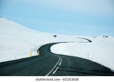 Scenery of the long and winding road to the Dettifoss, a famous waterfall in northeast Iceland. The black asphalt road with yellow street colonnade pillars contrast the snow alongside with blue sky.