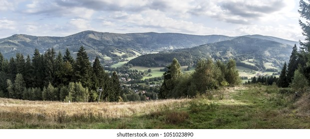 scenery of Moravskoslezske Beskydy mountains near Moravka village in Czech republic with ski slope, meadow, trail on grass, hills on the background and blue sky with clouds