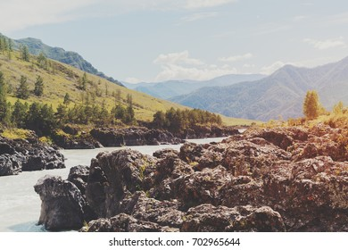 Scenery of the most narrow place of Katun river in Altai mountains with distant meadows and hills in haze and mossy huge stones in foreground, summer sunny day, Kuyus district, Russia
