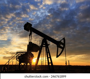 Scenery with oil and gas well pump and dramatic sunset