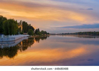 Scenery of orange sunset at the river, dramatic evening sky reflected in the water, Khmelnytskyi, Ukraine.