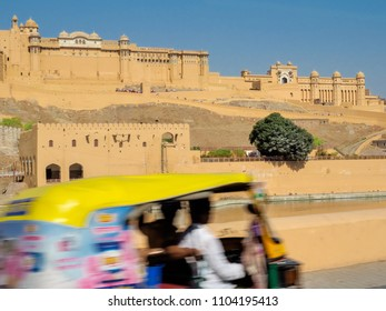 The scenery outside the Amber Fort  which is the landmark of  Jaipur city, Rajasthan State, India, while the blurry three-wheeled vehicle with passengers driving along the road