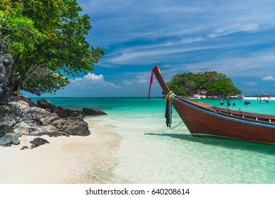 Scenery of paradise beach with small island and long tail boat parked on emerald green sea, Tup island, Krabi province, Thailand