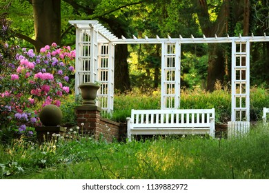 Scenery in a Park in spring: a white pergola, bench an flowering Rhododendrons on the left (Knoops Park , Bremen, Germany
