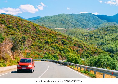 Scenery with red car in the highway in Carbonia near Cagliari in Sardinia in Italy. Nature and Automobile back in the road. Mountains and hills on the background