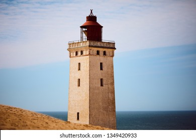 Scenery of Rubjerg Knude Fyr Lighthouse in Lønstrup Klint cliff, Denmark, located on North Sea coast, surrounded by sand dunes and viewed from the mainland.