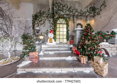 the scenery of the Studio or theater. Entrance in an old architecture with staircase and columns. Christmas decoration with garlands and fir branches