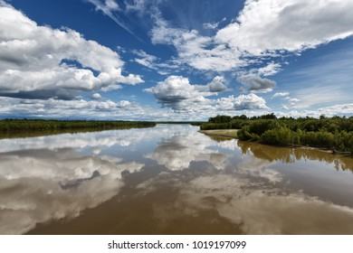 Scenery summer landscape of Kamchatka Peninsula: colorful view on Kamchatka River, beautiful blue sky with clouds and reflection in water. Eurasia, Russian Far East, Kamchatka Region. Copy space
