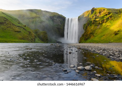 Scenery summer long exposure view of famous Skogafoss waterfall with reflection in stream surface