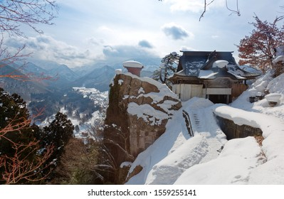 Scenery of sutra repository & founder's hall perched on a rocky cliff covered by heavy snow on a cold winter day, in Risshaku-ji, a famous Buddhist Temple & historic site in Yamadera, Yamagata, Japan