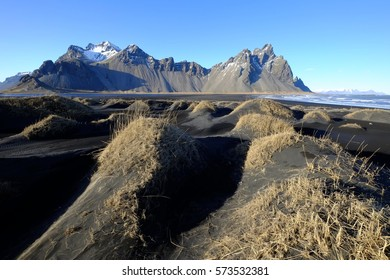 scenery of vestrahorn peaks at the end of winter at Stokkness,Iceland with clear blue sky.
