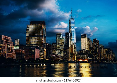 Scenery view of Lower Manhattan skyline at evening with city lights reflected in Hudson river. Beautiful New York cityscape view. Contemporary metropolis city in need of a huge amount of electricity