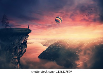 Scenery view as a wander girl silhouette on the edge of a cliff watching the beautiful sunset sky. Enjoy the silence and meditate as a balloon floating over the beautiful landscape. Feel free concept.