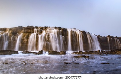 Scenery of waterfall and waterr flow couse by big wave from the ocean at Karang Taraje Bayah Banten Sawarna Beach Indonesia.