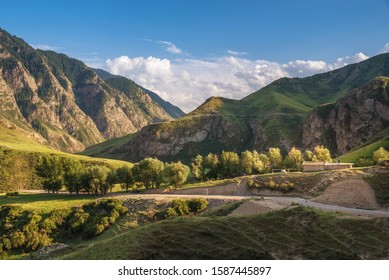 Scenery of the wriggle of mountains with rural farmhouse in sunlight and blue sky with clouds in the Tien Shan mountains in Xinjiang of China