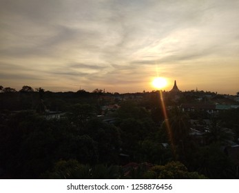 The scenery of Yangon city with silhouette of Shwedagon pagoda and smaller stupas during sunset in dim twilight, Myanmar
