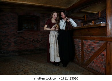 Scenes from life in a medieval tavern. Girls in historical costumes. Dress from the Middle Ages. Vintage fashion. Reconstruction of  medieval tavern. An inn with a tavern. Food and rye bread. Girl eat