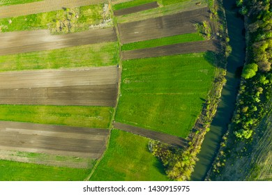 Scenic above view of farming plot of land near the river