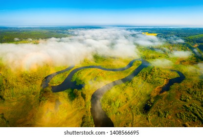 Scenic aerial landscape. Summer meadow with river under low white clouds early in the morning. Picturesque summer background. Aerial view. From above.
